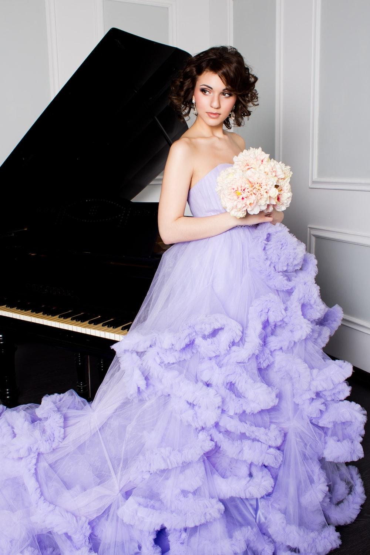 woman in purple off-shoulder dress holding bouquet of flowers