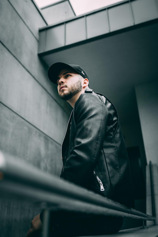 man in black leather jacket sitting on railings