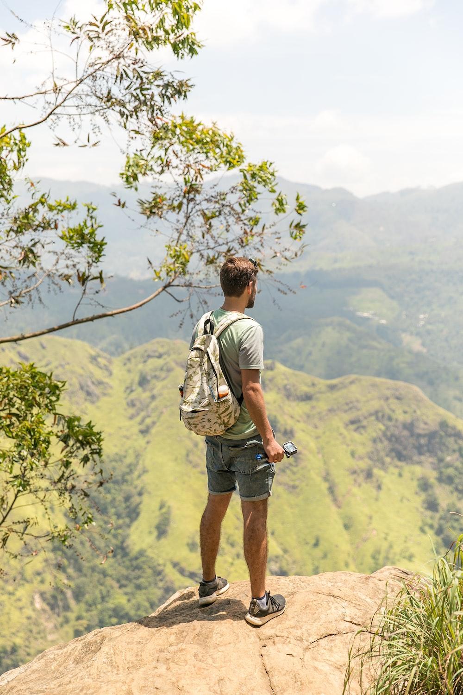man standing on cliff overlooking mountain