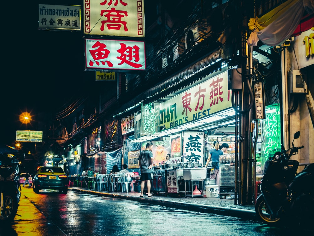 man standing beside store and road during nighttime