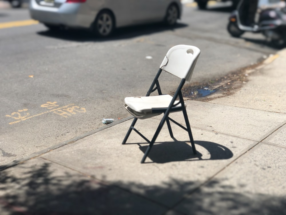white and black folding chair on roadside during daytime