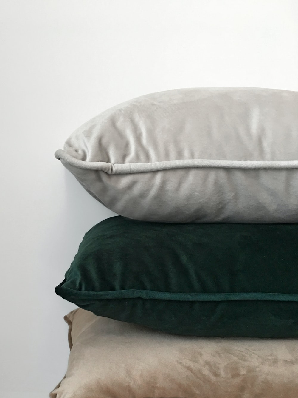 three assorted-color pillows