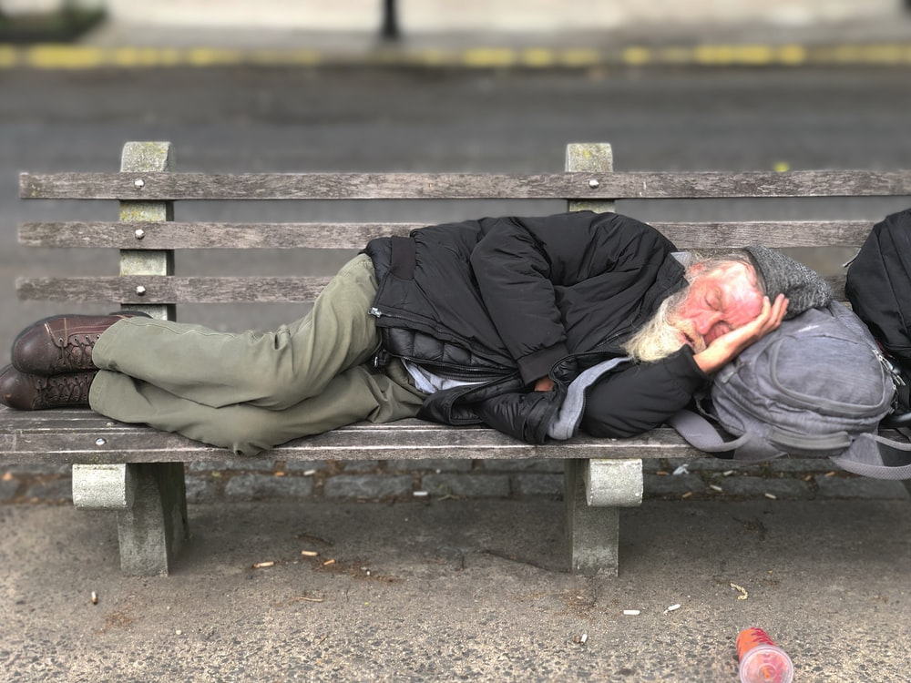 man sleeping on gray wooden bench near outdoor during daytime
