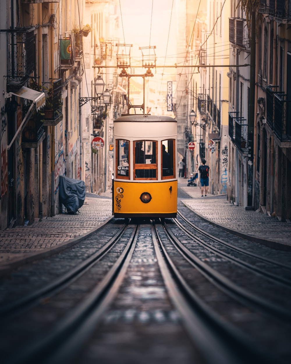 photography of yellow tram traveling on road during daytime