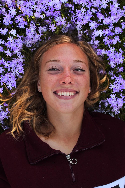 smiling woman near purple-petaled flower