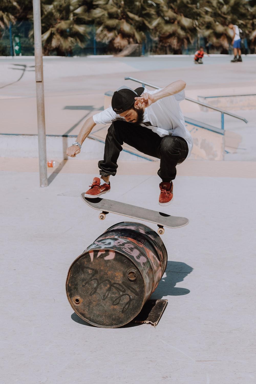 man jumping on black metal barrel with skateboard during daytime