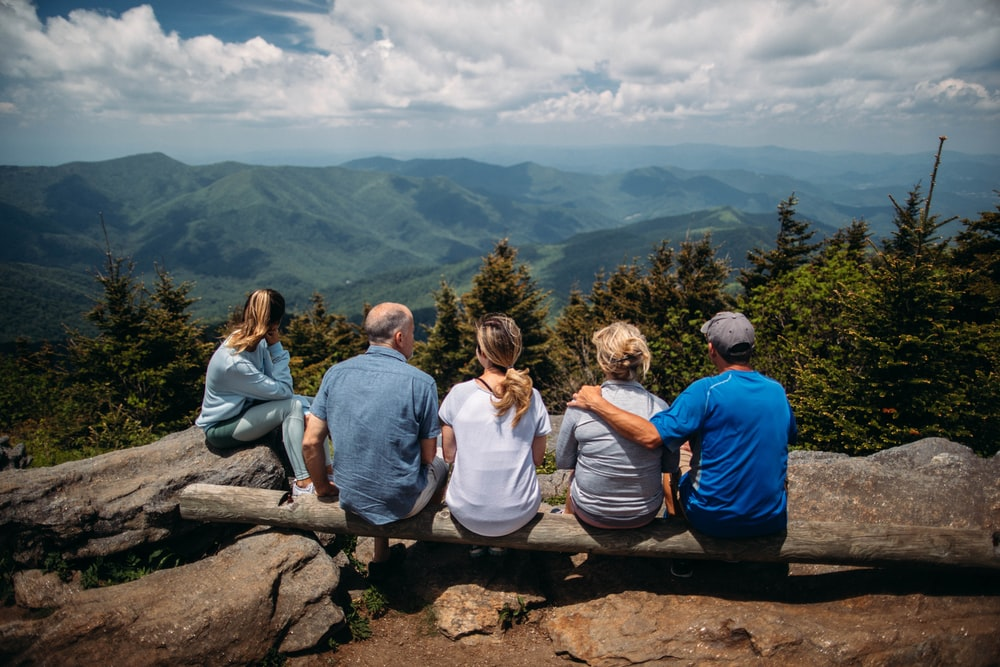 group of people sitting on rocks overlooking mountain