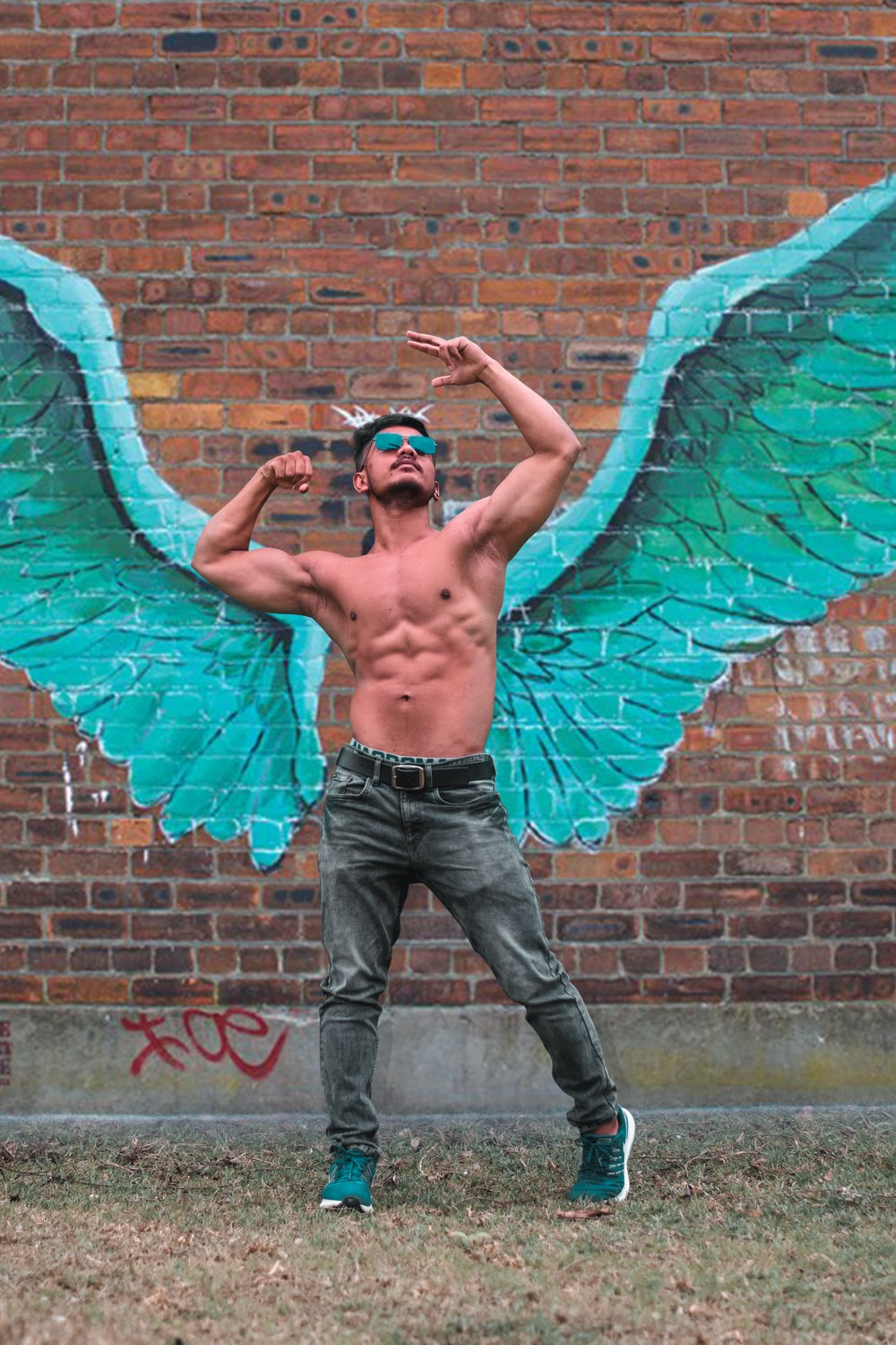 man in front of a painted green wings on brick wall