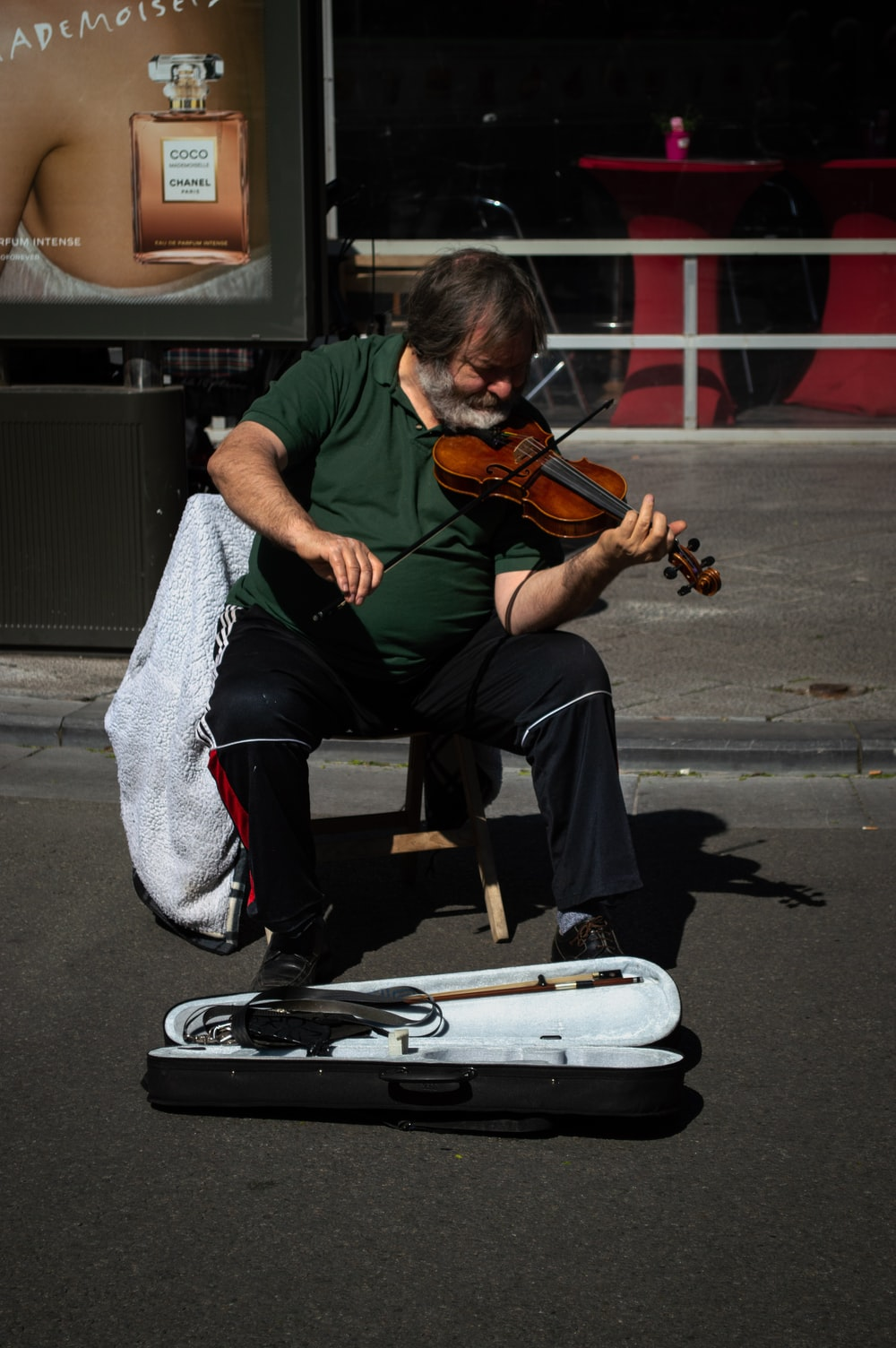 unknown person playing brown violin outdoors