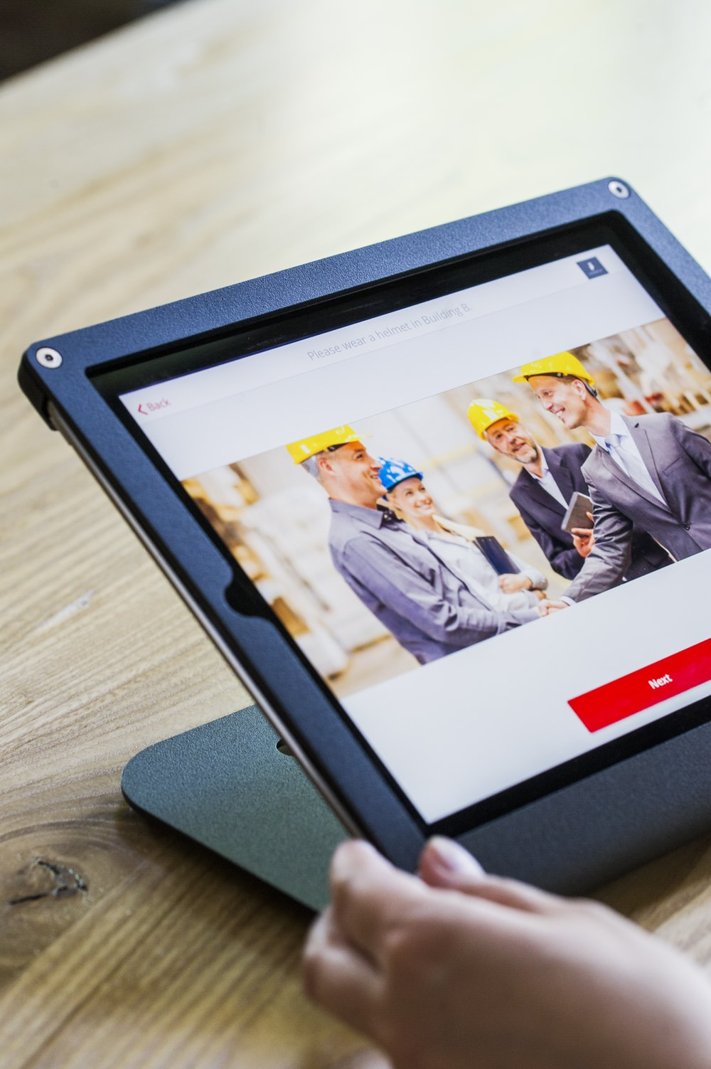 iPad with four business persons shaking hands display