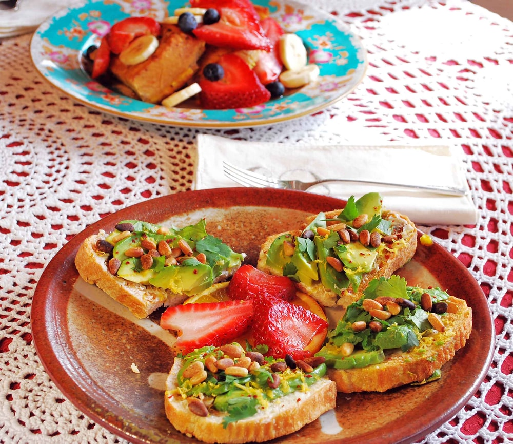 baked bread with sliced fruits on brown plate avocado toast