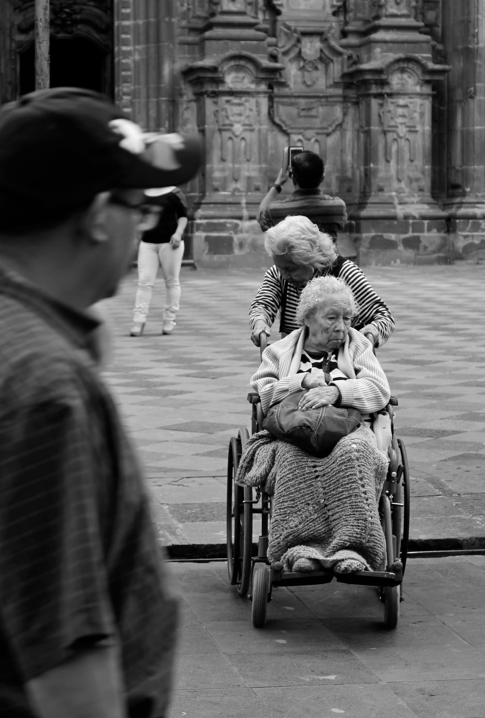 grayscale photography unknown person riding on wheelchair outdoors
