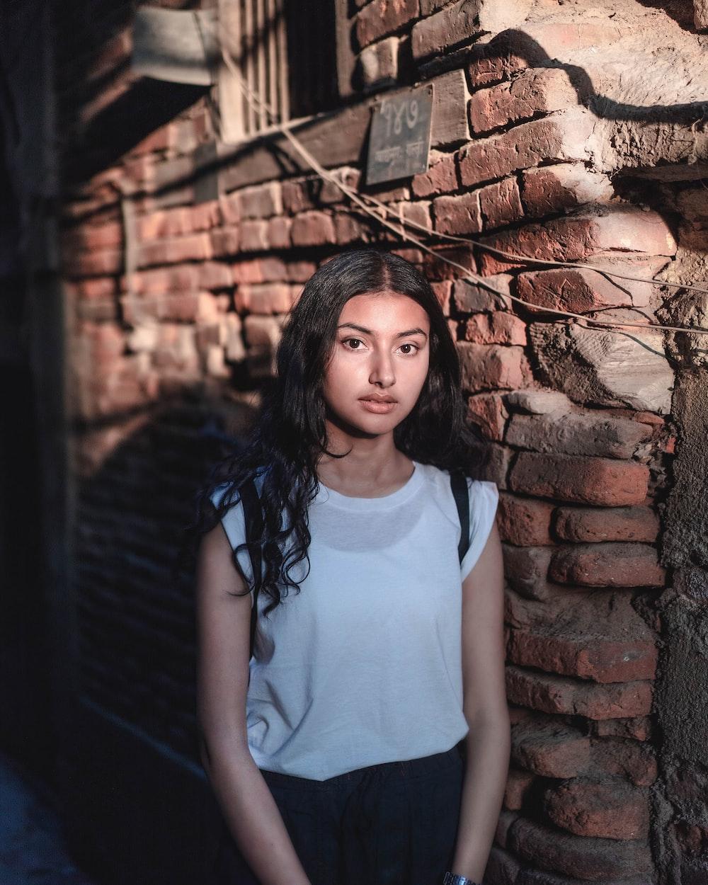 woman standing beside brown brick wall