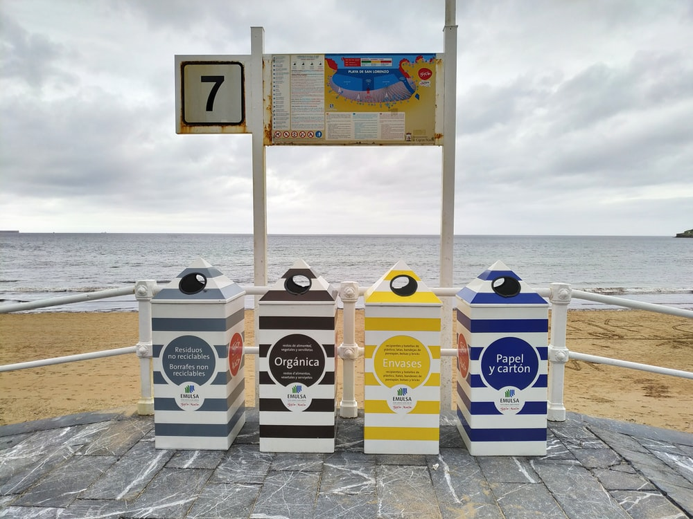 gray, black, yellow, and blue trash bins