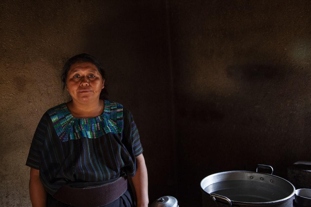 woman teal and black dress standing near stock pot