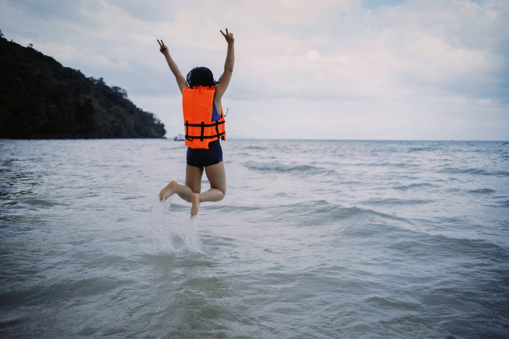 woman wearing life vest jumping into sea