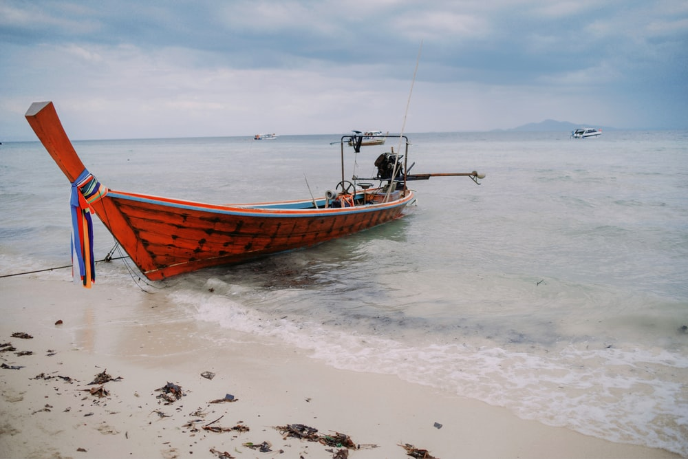 brown wooden canoe at beach