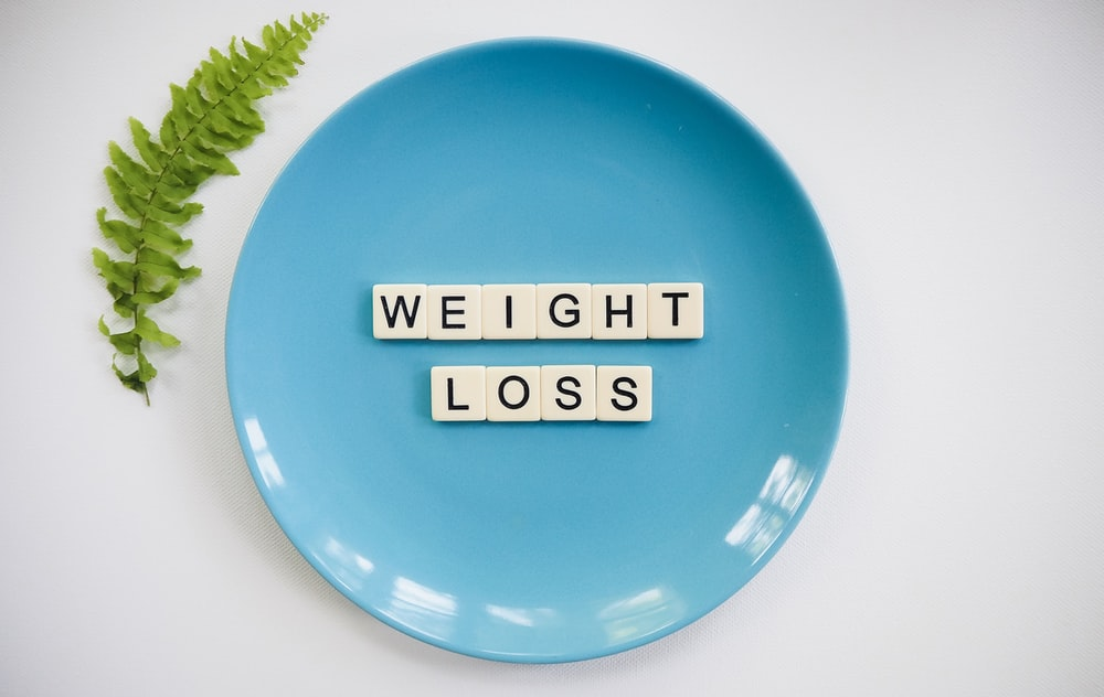 flat lay photography of weight loss tiles on teal ceramic plate beside green Boston fern leaf