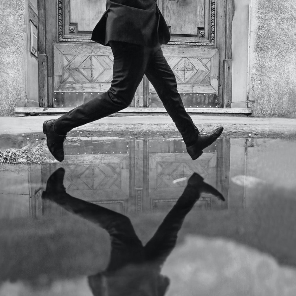 grayscale photography of unknown person running outdoors