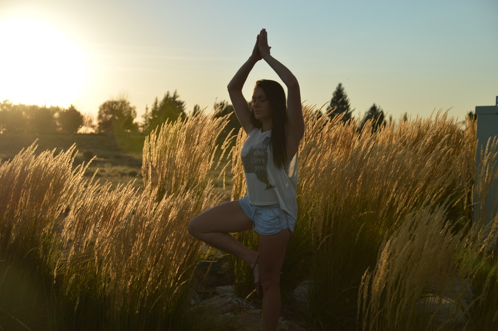 woman doing yoga pose outside near grass