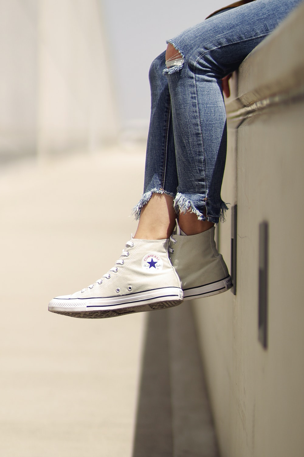 woman wearing white Converse low-top sneakers