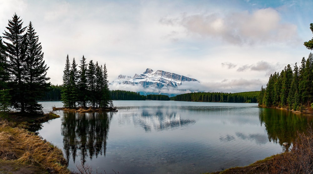 landscape photo of snow covered mountain near body of water during daytime