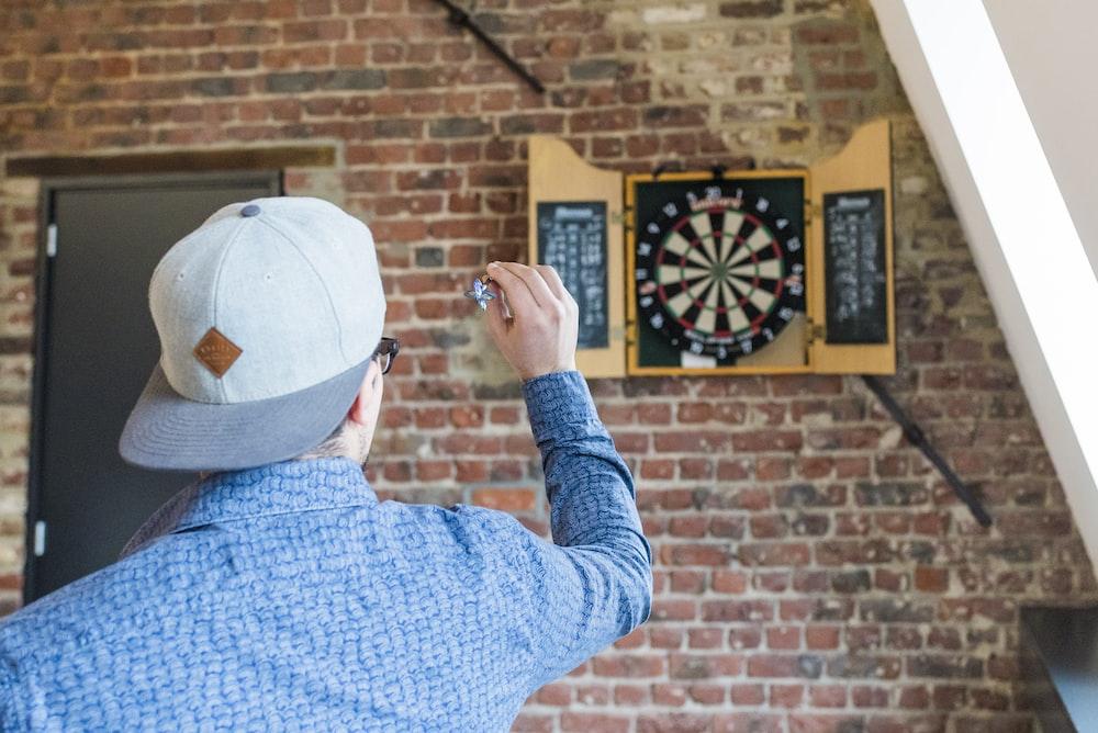 man in blue dress playing dart