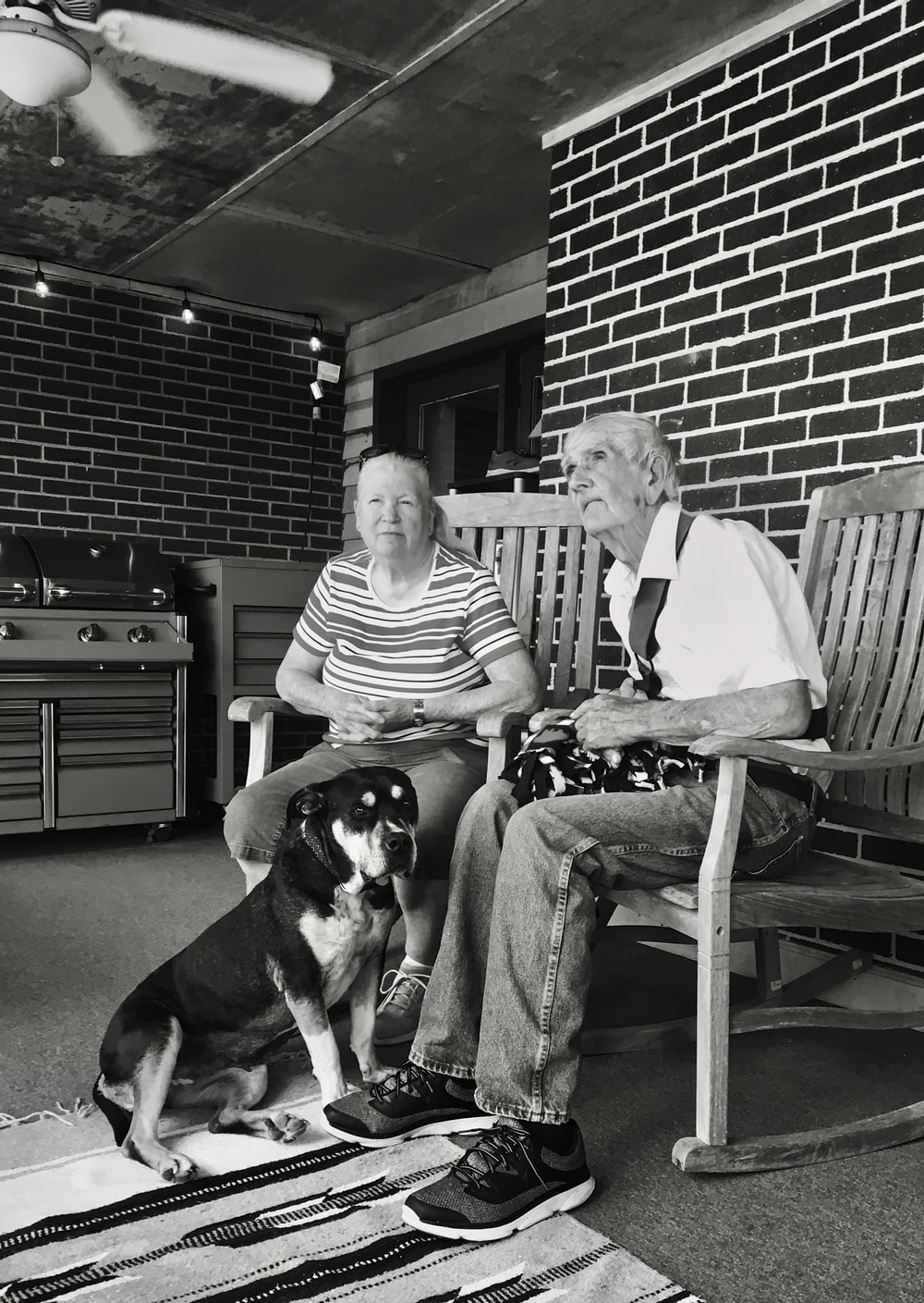 grayscale of man and woman sitting on wooden rocking chairs