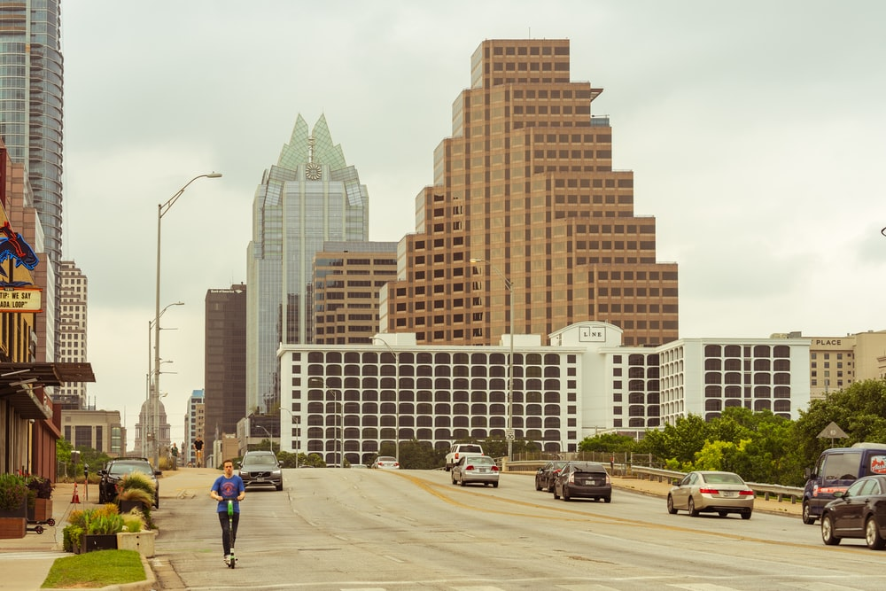 cars passing by buildings during daytime