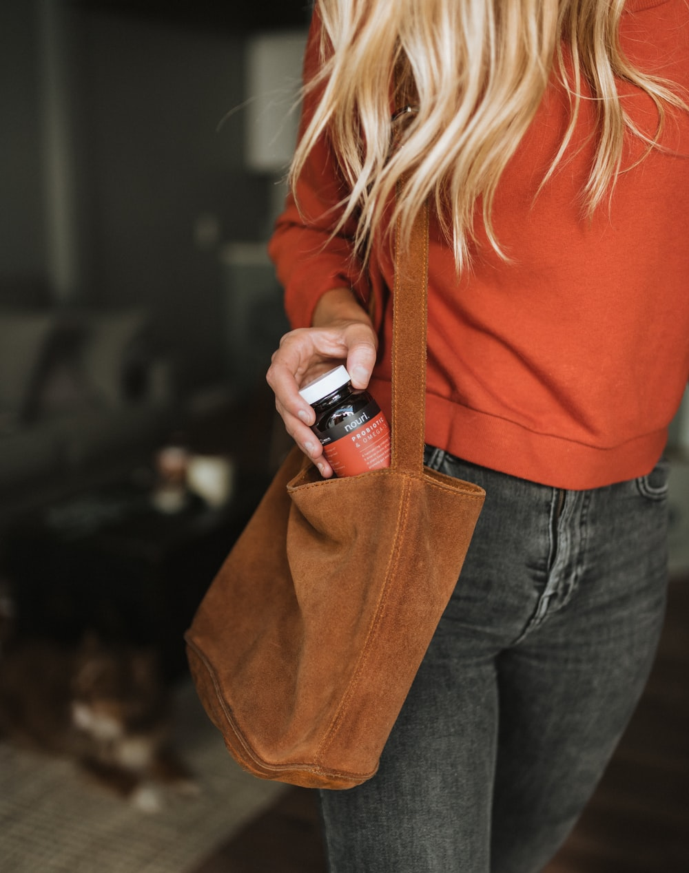 woman holding bottle on bag