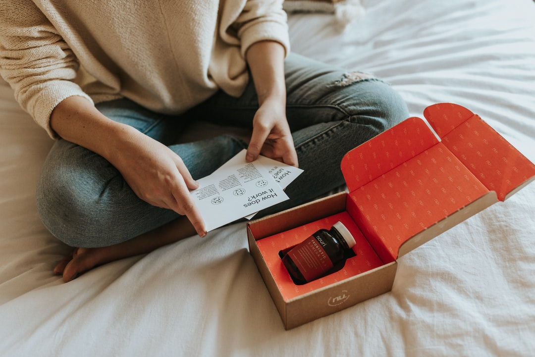 Woman sitting on bed while reading package materials included within the Nouri subscription box.