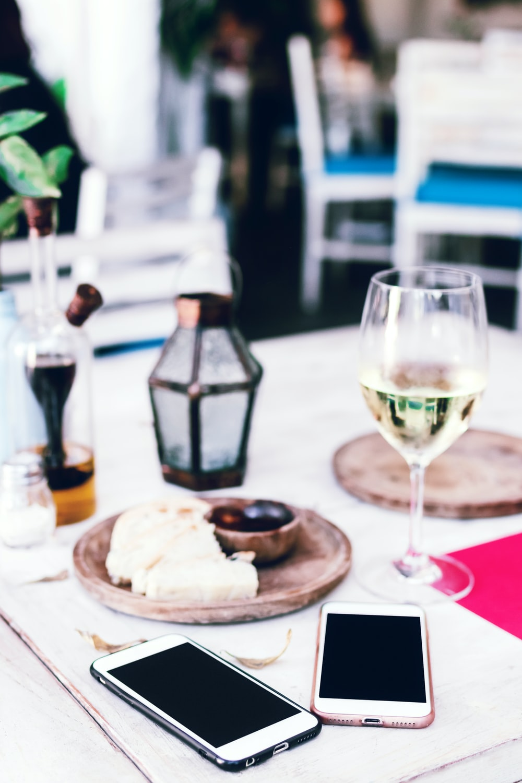 two smartphones beside wine glass