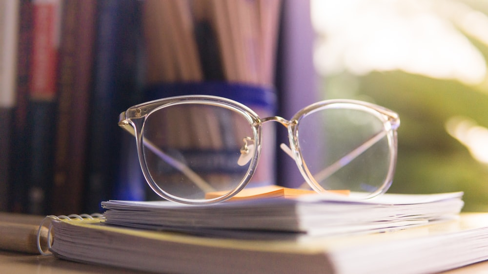 clear eyeglasses on pile of notebooks