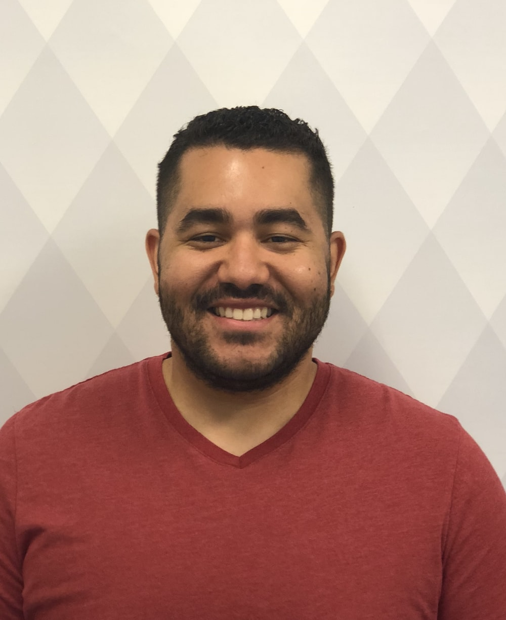 man smiling wearing maroon V-neck shirt