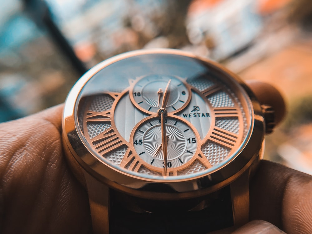 round gold-colored chronograph watch