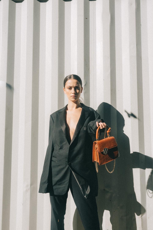 woman wearing black blazer holding brown handbag leaning on white wall