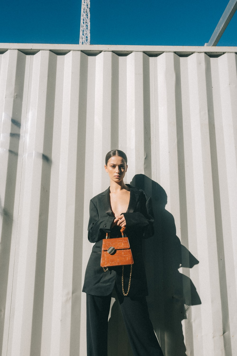 woman carrying leather handbag while standing near wall