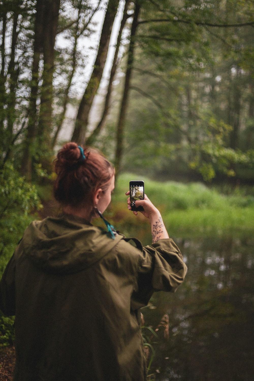 woman wearing jacket taking photo of trees