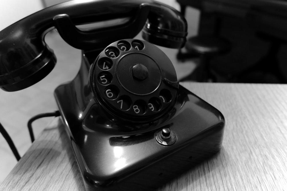 shallow focus photo of black rotary telephone