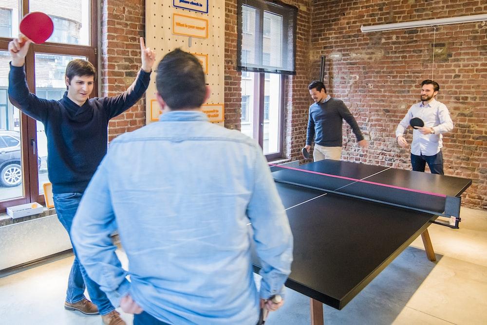 four men playing table tennis