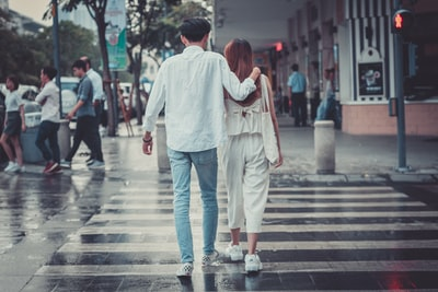man and woman crossing pedestrian lane asphalt teams background