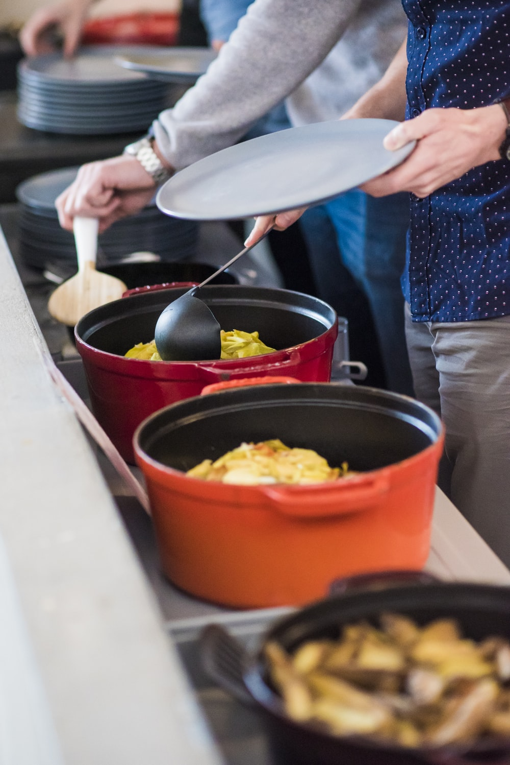 two red and orange cast-iron cooking pots