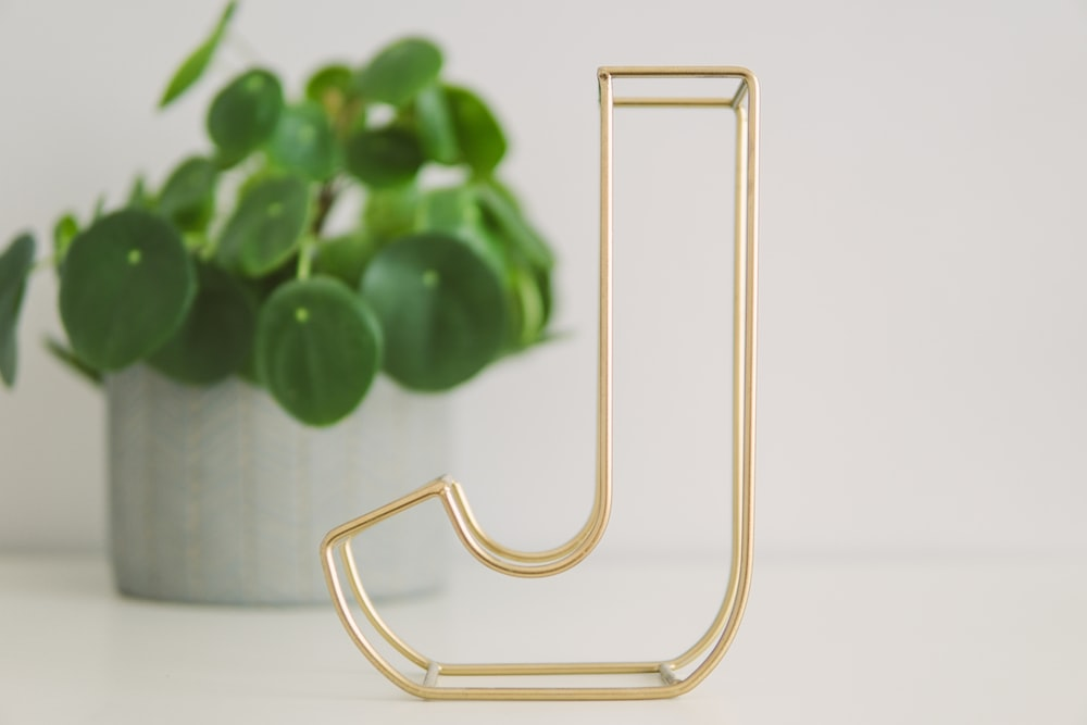brass-colored decorative marquee letter J on table