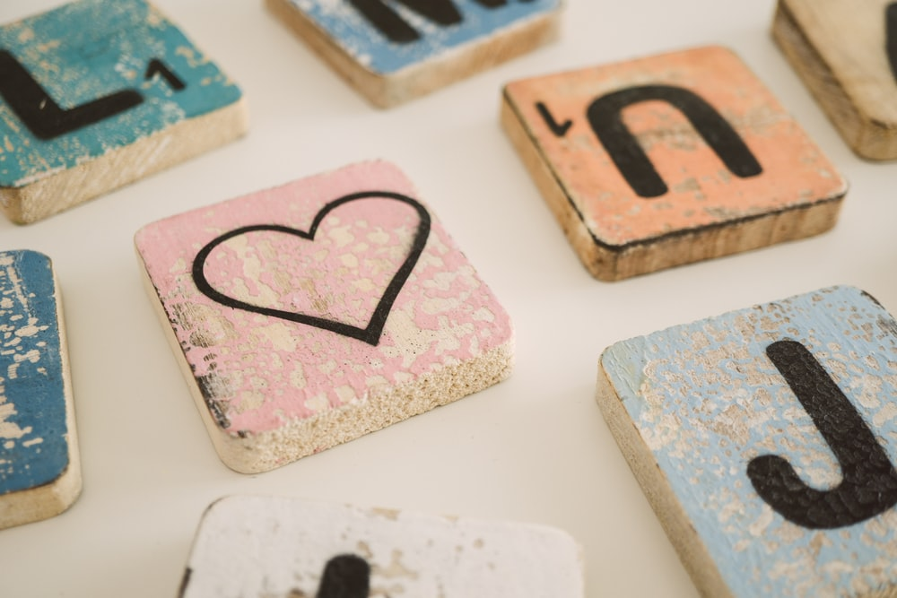 scrabble blocks and heart block on white surface