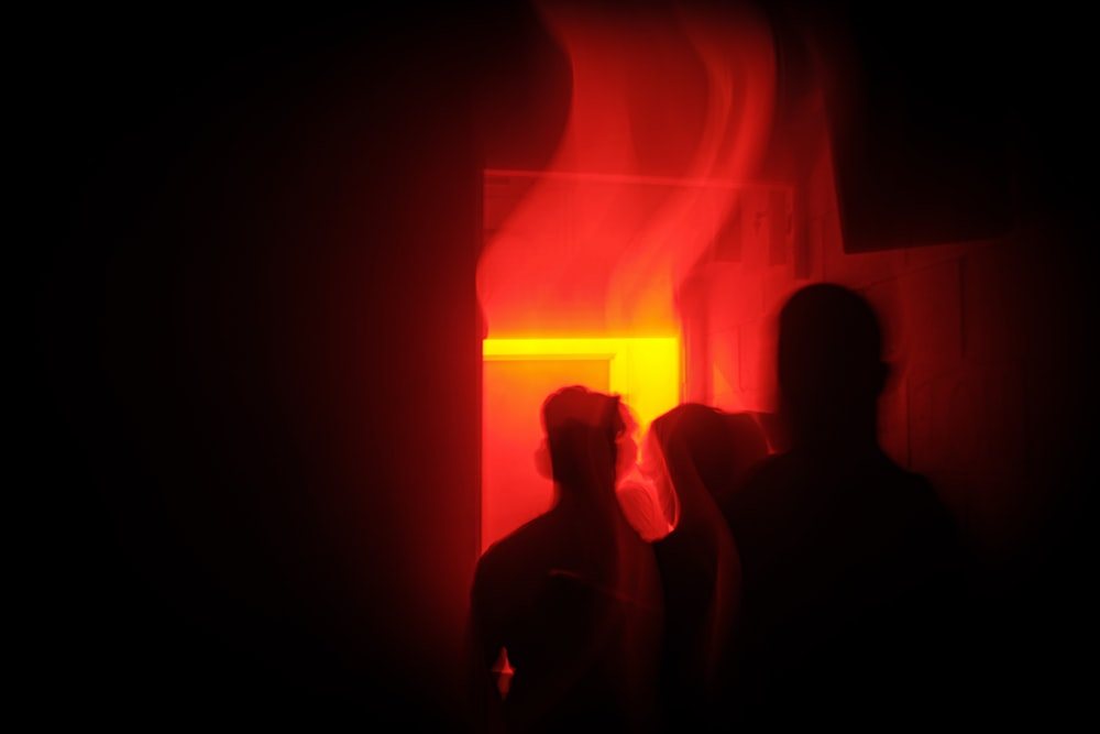 silhouette of people inside red lighted room