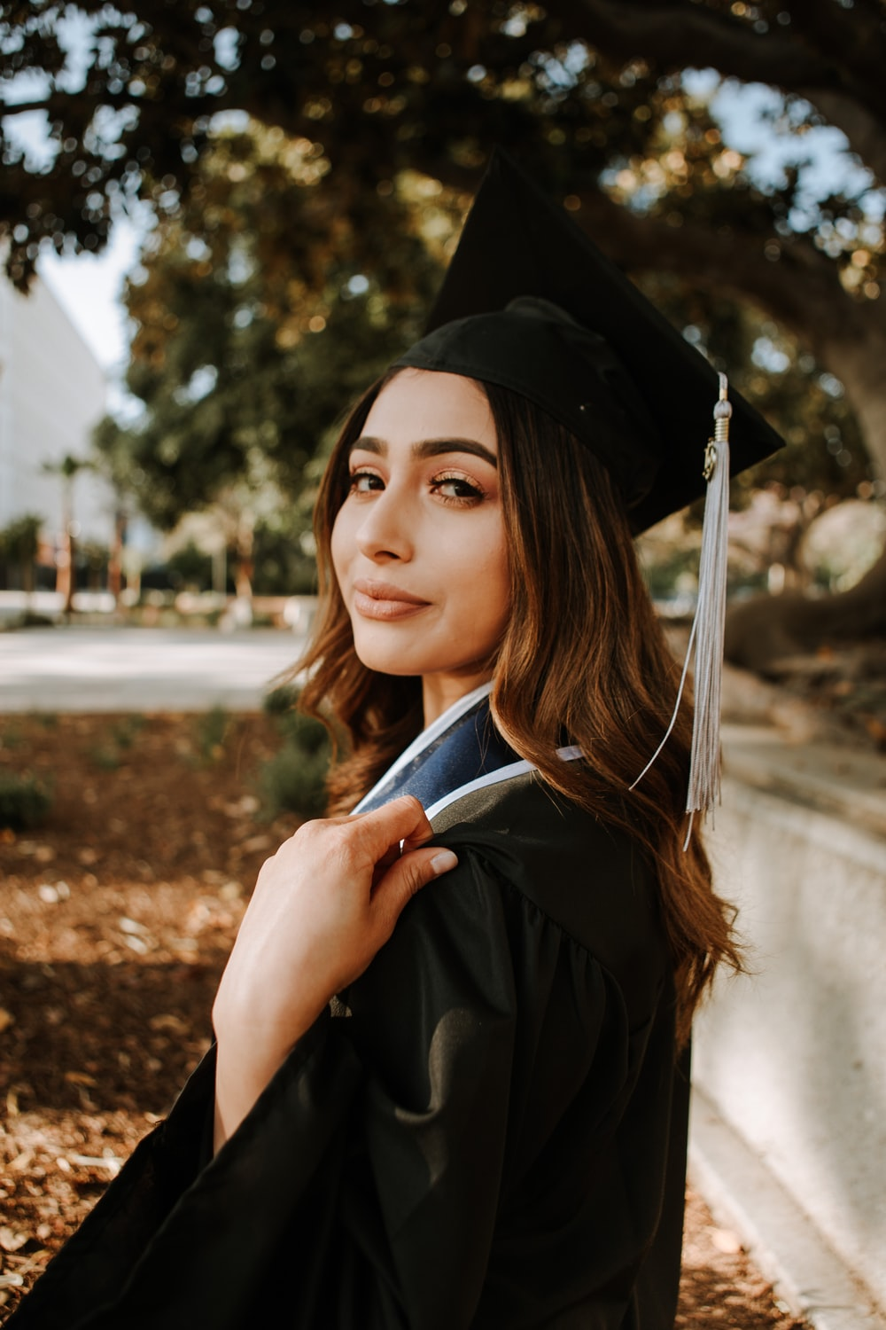 woman in black graduation gown with black mortar board