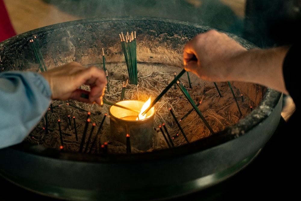 man in black shirt lighting green incense candle