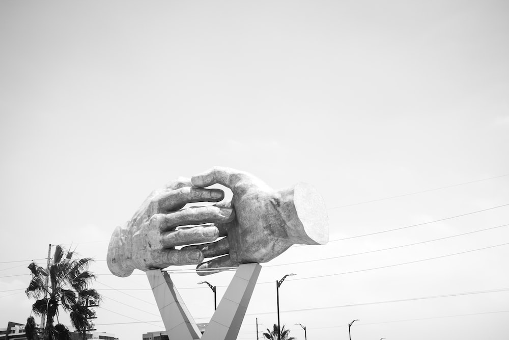 grayscale photo of shaking hands statue