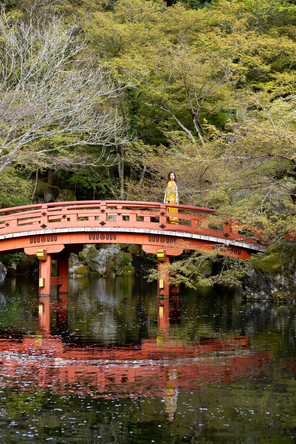 woman standing on red arch bridge surrounded by trees at daytime