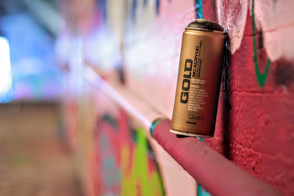 Gold can beside wall